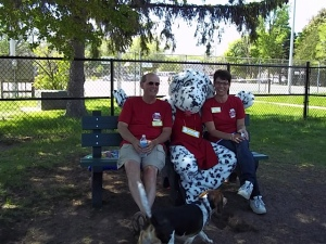 Chris and Karry Borolo, founders of D.O.G. Bakery, sitting on bench at dog park with their 'human' dog Bisquit